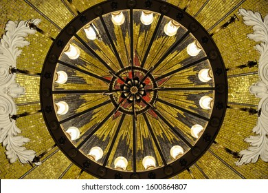 MOSCOW, RUSSIA - December 04, 2019 Directly below view of illuminated chandelier hanging from dome in intermediate hall of Komsomolskaya Ring-line station. decorated with mosaic panel with red star