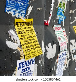 Moscow, Russia - December 08, 2018. Paper advertisements on the shabby wall. Illegal announcement of registration in Moscow for the foreigners close up. Writing on russian: registration, medical books