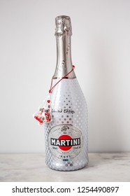 MOSCOW, RUSSIA - DECEMBER 10, 2018: Bottle of Quality Aromatic Sparkling Wine Martini Asti with Red Christmas Toy Tree on White Wall Background. Limited Edition. Product of Italy.