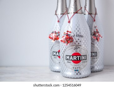 MOSCOW, RUSSIA - DECEMBER 10, 2018: Three Bottles of Quality Aromatic Sparkling Wine Martini Asti with Red Christmas Toys Trees on White Wall Background. Limited Edition. Product of Italy.