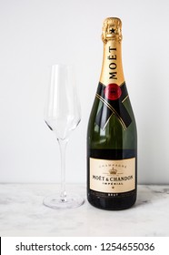 MOSCOW, RUSSIA - DECEMBER 10, 2018: Moët & Chandon Imperial Champagne Bottle and One Glass on White Wall Background. Product of France.