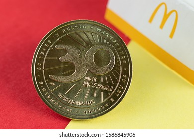 Moscow, Russia - December 12, 2019: сoin issued McDonald's Restaurant in honor of 30 years in Russia (MacCoin). Defocused McDonald's logo on background. Close up, focus on foreground