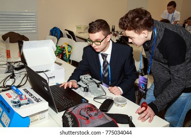 MOSCOW/ RUSSIA - DECEMBER 13, 2017. Two school boys with laptop, programming the robot at robotics competitions.