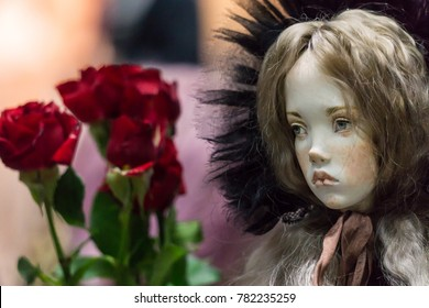 """Moscow, Russia, December 16th 2017. Exhibition """"The art of the doll"""".  A doll of a sad girl in a 19th century bonnet with red roses at the background"""