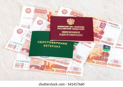 """MOSCOW, RUSSIA - DECEMBER 18, 2016: Russian Pension Certificate, Veteran Certificate lying over banknotes. Text in russian: """"Russian Ministry of Defense"""", """"Pension Certificate"""", """"Veteran Certificate"""""""