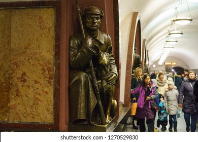 Moscow / Russia - December 18 2018: Moscow metro station interior. Statue of a red guarder with a dog in the Ploshchad Revolyutsii/Revolution square metro station