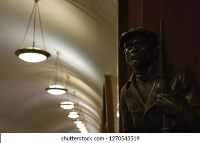 Moscow / Russia - December 18 2018: Moscow metro station interior. Statue of a red guarder with a gun in the Ploshchad Revolyutsii/Revolution square metro