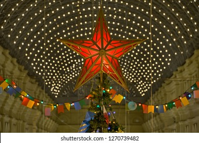 MOSCOW, RUSSIA - December 19, 2018 Festive illustration with neon effect of the copy of kremlin ruby star decorating the top of a Christmas tree under a glass roof in GUM shopping mall at Red Square.
