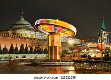 MOSCOW, RUSSIA - December 19, 2018 Evening view of the colorful spinning carousel at the corner of the Christmas and New year's fair at the Red square in the snowfall.