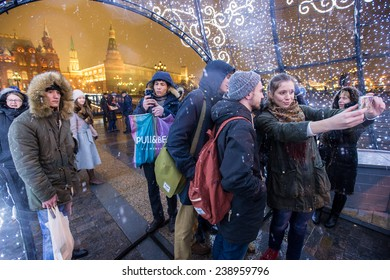 MOSCOW, RUSSIA - DECEMBER 19: Muscovites and guests from central asia take a photo on Manezhnaya Square decorated for New Year  celebration on December 19, 2014 in Moscow, Russia.