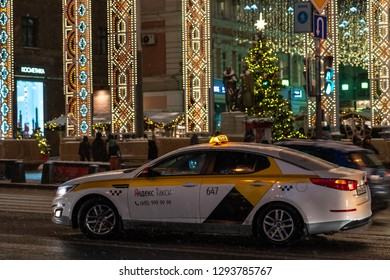 Moscow, Russia - December 22, 2018: Taxi rides in the evening in the center of Moscow, decorated for the New Year