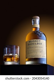 Moscow, Russia - December 22, 2020. Bottle of Monkey Shoulder whiskey and glass with drink and ice on wooden table on brown background with copy space.