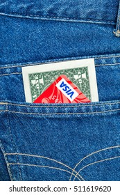 MOSCOW, RUSSIA - DECEMBER 25, 2015: One american dollar and Credit card Visa sticking out of the blue jeans pocket