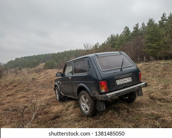 Moscow, Russia - December 25, 2018: Black Russian off-road car Lada Niva 4x4 (VAZ 2121 / 21214) parked on the field.