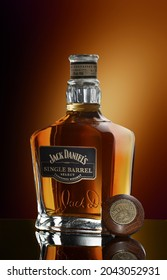 Moscow, Russia - December 25, 2020. Bottle of Jack Daniel's whiskey and glass with drink and ice on wooden table on brown background with copy space. Brand of the American whiskey