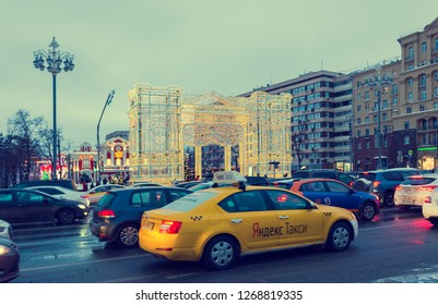 MOSCOW, RUSSIA - DECEMBER 27, 2018: Festive new year lights of evening Moscow, Yandex taxi on Tverskaya street