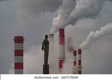 Moscow, Russia - December 29, 2019: Industrial silhouettes of Moscow city. Yury Gagarin monument in Moscow in winter overcasting day. Heat station pipes are nearby. Long exposure photography.