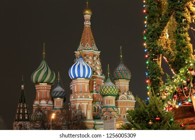 Moscow, Russia, December 4, 2018. View of the domes of St. Basil's Cathedral and New Year's decorations on trees in Red Square in the evening city