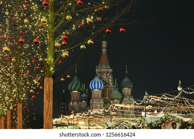 Moscow, Russia, December 4, 2018. New Year decorations on the trees in Red Square and the view of the domes of St. Basil's Cathedral, the night city