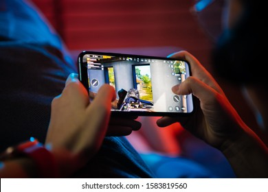 MOSCOW, RUSSIA - December 6, 2019: Close up gamer hand holding a smartphone with Playerunknown's Battlegrounds also known as PUBG online shooting game. It is an online multiplayer battle game.
