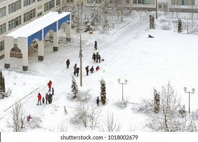 MOSCOW, RUSSIA - FEBR 5, 2018: Snow-covered Moscow. School students after lessons play with snow in schoolyard after heavy snowfall