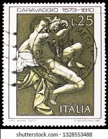 """MOSCOW, RUSSIA - FEBRUARY 10, 2019: A stamp printed in Italy shows Painting """"Saint John the Baptist"""" by Caravaggio, 4th centenary of the birth of Michelangelo Merisi, the Caravagio serie, circa 1973"""