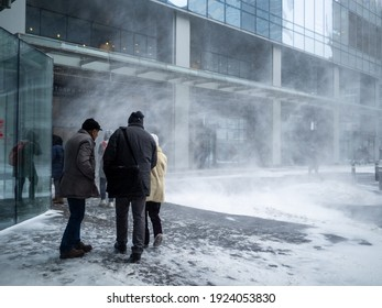 Moscow. Russia. February 12, 2021. Natural disasters. People walk along the building through a blizzard with heavy snowfall. A snow cyclone covered the city.