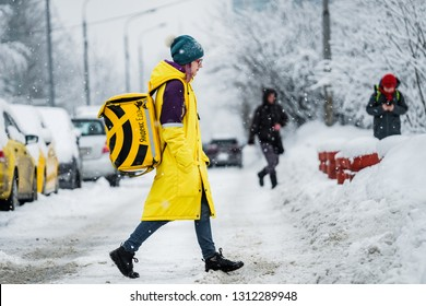 MOSCOW, RUSSIA - FEBRUARY 13, 2019: The girl from the food delivery service Yandex.Food goes on snow-covered Moscow.