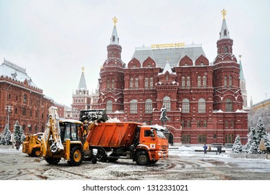 MOSCOW, RUSSIA - February 13, 2019 Snow cleaning tractor loading the snow on a huge track at Manezhnaya Square in the background of the building of State Historical Museum.