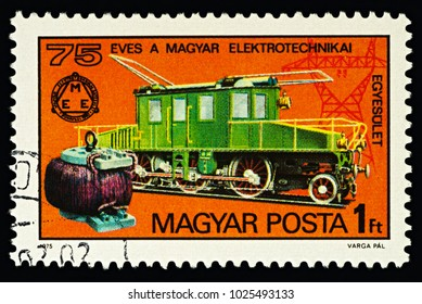 Moscow, Russia - February 15, 2018: A stamp printed in Hungary, shows Kando electric locomotive and early transformer, dedicated to the 75th Anniversary of Hungarian Electrotechnical Union, circa 1975