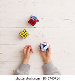 Moscow, Russia, February 16 2018: Rubik's snake puzzle, closeup, and Rubik's cubes laying on white wooden background. Woman holding Rubik's puzzle toy and playing with it.
