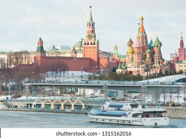 """MOSCOW, RUSSIA - FEBRUARY 16, 2019: """"Floating bridge"""" in the park """"Zaryadye"""", Spasskaya Tower, Cathedral of Vasily the Blessed (Saint Basil's Cathedral) on Red Square and Radisson Royal Flotilla yacht"""