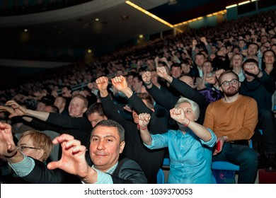 Moscow, Russia - February 19, 2018: audience at the business conference for entrepreneurs `Transformation`. Warm-up for the audience - all raised their hands up and stretch upwards
