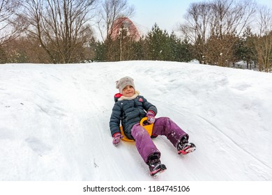 Moscow, Russia - February 2018: Joyful Children ride from the ice hill on sledges and snow tubing in the Park  territory of Serebryany Bor island in Khoroshevo-Mnevniki district.