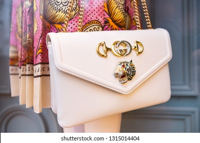 Moscow, Russia - February 2019: Beige Women's Gucci Cross Bag With Gold Chain Close-Up On Background Of Dress With Print From New Collection.