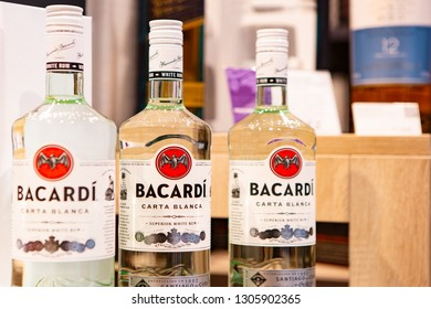 Moscow, Russia - February 2019: Three Bottles Of Alcohol - White Rum Bacardi With Selective Focus On Blurred Shelf Background With Alcohol.