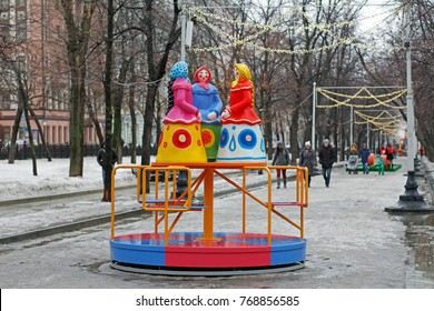 """Moscow, Russia - February 21, 2017: Traditional Dymkovo toy three women in headscarves as art object and Children's carousel at Russian national festival """"Shrove"""" in Tverskoy Boulevard in Moscow"""