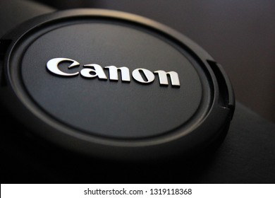 Moscow, Russia - February 21, 2019: Canon camera lens cap close up view. Canon corporation brand logo on the cap cover for camera and photo equipment. Detailed view of classic black Canon camera cap