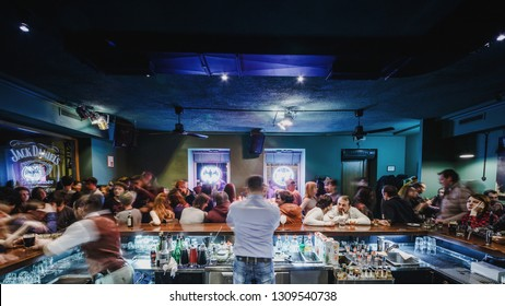 Moscow, Russia - February 22, 2015: Upscale bar is busy with a view behind bartender working for a crowd of patrons