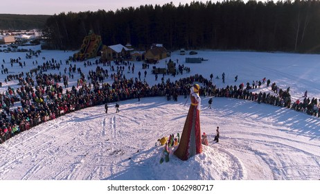 Moscow, Russia - February 26, 2018: Aerial view of Traditional burning of Maslenitsa Scarecrow. Burning of Scarecrow. Aslenitsa celebration. Man sets fire to a big doll-scarecrow on a stage in a city
