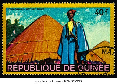 """Moscow, Russia - February 27, 2018: A stamp printed in Guinea shows man in traditional clothes in African village, Fouta-Djallon - Middle Guinea, series """"Regional Costumes and Habitations"""", circa 1968"""