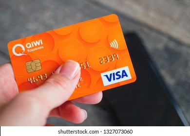 Moscow, Russia,  February 27, 2019. Plastic card VISA  Russian QIWI Wallet bank in hand