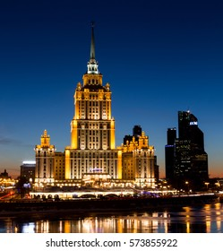 Moscow, Russia - February 5, 2017: Radisson Royal Hotel, Moscow International Business Center - symbols of Stalin and Putin eras. Colorful lights and reflections in the Moskva River in the evening.