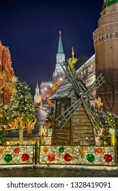 MOSCOW, RUSSIA - Festive decorations on Manezhnaya Square near Moscow Kremlin and Red Square with miniature old style wooden windmill for the ancient Russian folk holiday, Maslenitsa (pancake week)