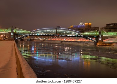 MOSCOW, RUSSIA - Festive pedestrian bridge of Bogdan Khmelnitsky with reflection on water of the river Moskva (Moscow) and Rostovskaya embankment spotted with colorful lights during winter holidays.