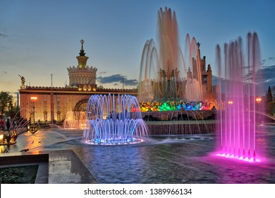"MOSCOW, RUSSIA - Huge water pool of restored ""Stone Flower"" fountain illuminated with colorful spotlights on the grounds of VDNKh park and exhibition at nice spring evening in twilight."