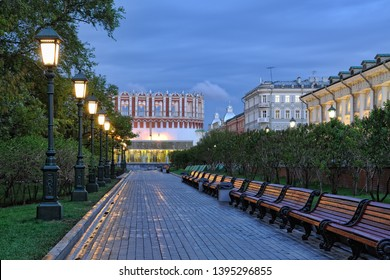 MOSCOW, RUSSIA - Illuminated by old-style streetlights, beautiful alley in Alexander Garden with wooden benches on the way to Kutafya Tower of Moscow Kremlin in early morning twilight in spring season