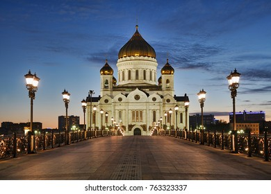 MOSCOW, RUSSIA - Illuminated by powerful floodlights majestic Cathedral of Christ the Savior framed with old style street lights of Patriarchy Bridge at spring twilight.