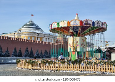 MOSCOW, RUSSIA - Jan 25, 2018 Colorful children's carousel at GUM fair on Red Square in the background of the Kremlin's wall and Senate building with the flag of Russia hoisted at the top of its dome.