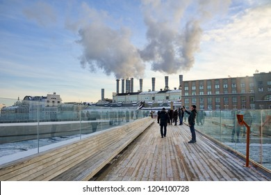 MOSCOW, RUSSIA - Jan 25, 2018 People walking and taking photos on hovering bridge over Moskva River in park Zaryadye in background of steam rising up from chimneys of oldest in Russia power plant #1